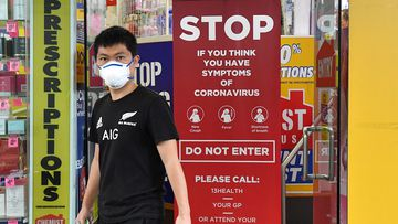 A customer wearing a protective face mask is seen leaving a pharmacy on Edward Street in Brisbane, Monday, March 23, 2020. (AAP Image/Darren England) NO ARCHIVING
