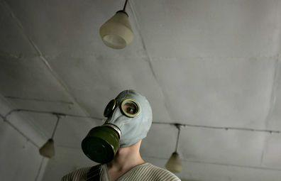 Ukraine student tries on gas mask near Chernobyl contamination zone