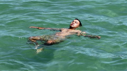 A man keeps cool in the water at Glenelg beach during yesterday's scorcher in Adelaide.