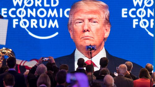 Participants watch US President Trump on a screen during the 48th Annual Meeting of the World Economic Forum. (AAP)