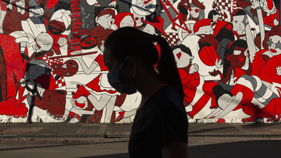 A woman wearing a mask walks past a wall mural in Prahran on September 06, 2020 in Melbourne, Australia.