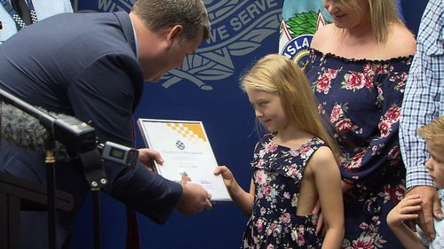 Addison is presented with a Certificate of Appreciation, a koala cop and a junior police cap she'll have to grow into. Picture: 9NEWS