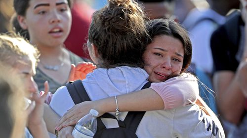Students embrace at Marjory Stoneman Douglas High School in Parkland, Florida, after the mass shooting.