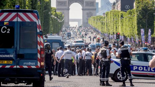 The Arc de Triomphe can be seen in the background of a police incident on the Champs Elysees in Paris. (AAP)