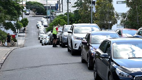 The cars of Brisbane residents as they wait to be tested for coronavirus.