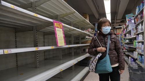 A woman wearing face mask walks past empty shelf of tissue papers at supermarket in Hong Kong, Thursday, Feb. 6, 2020