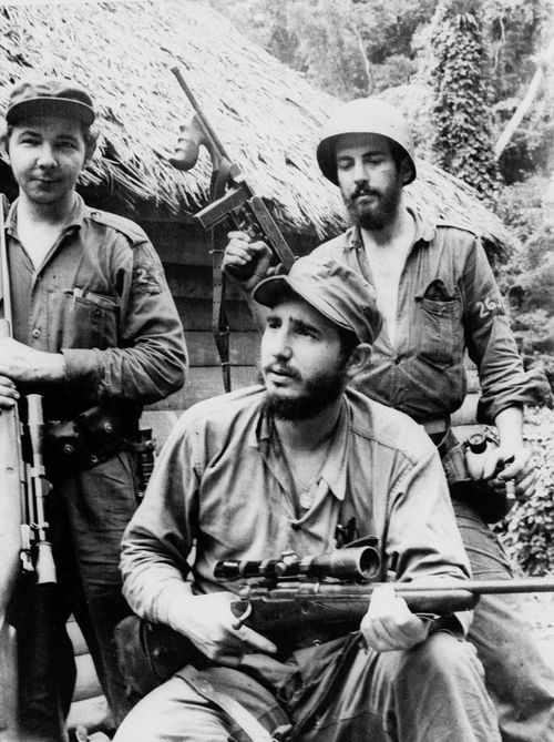 In a photo from 1957, a young Fidel Castro, the young anti-Batista guerrilla leader, center, is seen with his brother Raul Castro, left, and Camilo Cienfuegos, while operating in the mountains of eastern Cuba. (AAP)