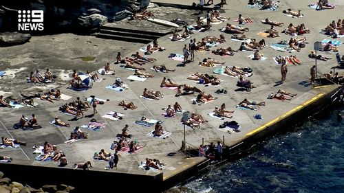 At Clovelly people appear to be spaced out on the concrete at the water's edge.