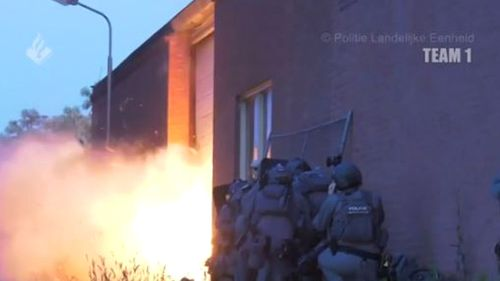 Police detonate an explosive to force their way into a building.