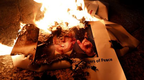 Palestinians burn the picture of the US Vice President Mike Pence during a protest against Mr Trump's decision to announce Jerusalem as the capital of Israel and the visit of Pence in the West Bank city of Bethlehem. (EPA)