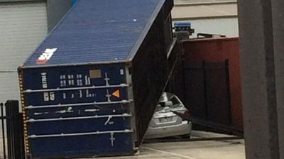 A car is crushed by a fallen shipping container. (Twitter)