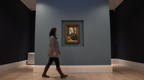 A member of the staff walks past the painting 'Young Man Holding a Roundel' by the Italian Renaissance painter Sandro Botticelli at Sotheby's, in London, Wednesday, Dec. 2, 2020