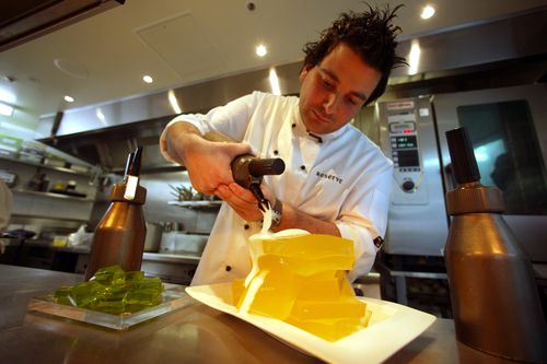 In this 2003 file photo, George Calombaris applies the finishing touches to a gin and tonic jelly with champagne foam.