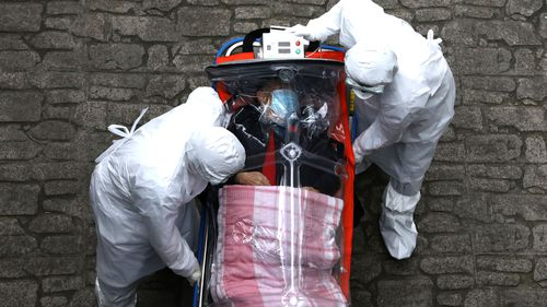 Medical staff in protective gear move a patient infected with the coronavirus from an ambulance to a hospital in Seoul, South Korea.