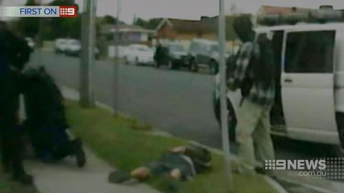 Officers from the Special Operations Group tackle Nicholls on a Geelong nature strip. (9NEWS)
