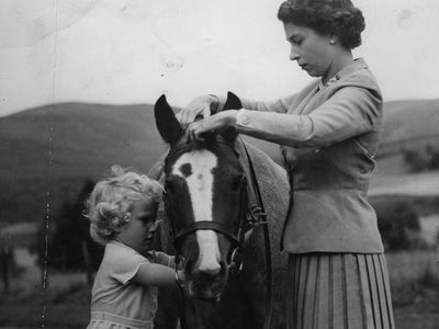 Princess Anne helping saddle a pony, 1955