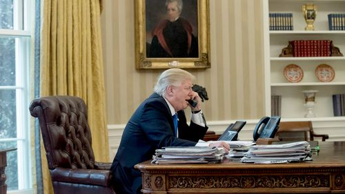 A file photograph shows US President Donald Trump making a phone call from the Oval Office of the West Wing.