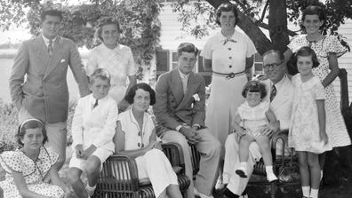 A portrait of the Kennedy family as they sit in the shade of some trees, Hyannis, Massachussetts, 1930s. Seated from left are: Patricia Kennedy (1926 - 2006), Robert Kennedy (1925 - 1968), Rose Kennedy (1890 - 1995), John F Kennedy (1917 - 1963), Joseph P Kennedy Sr (1888 - 1969) with Edward Kennedy on his lap; standing from left are: Joseph P Kennedy Jr (1915 - 1944), Kathleen Kennedy (1920 - 1948), Rosemary Kennedy (1918 - 2005), Eunice Kennedy (rear, in polka dots), and Jean Kennedy. (Photo b