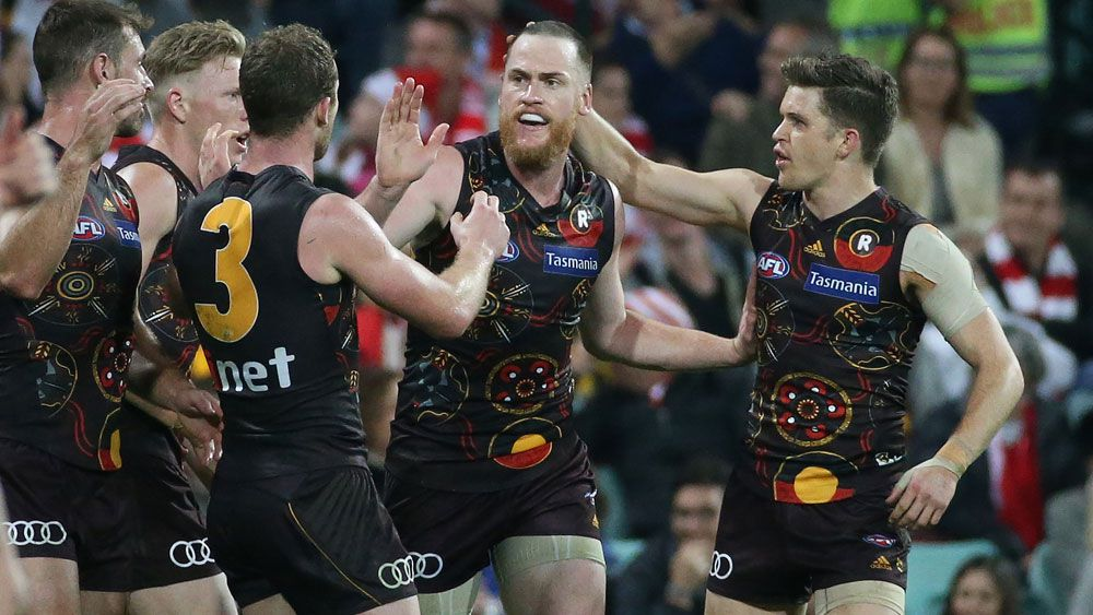Jarryd Roughead is swamped by teammates after kicking the winning goal against the Swans. (AAP)