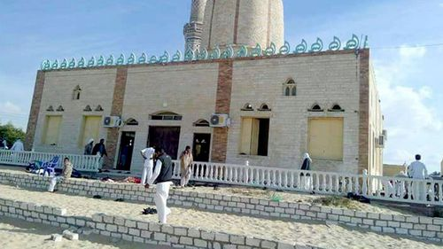 People walk outside a mosque that was attacked in the northern city of Arish, Sinai Peninsula, Egypt. (AAP)