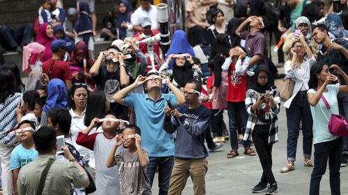 Stargazers look up at the sun with protective glasses to watch the solar eclipse from Jakarta, Indonesia.