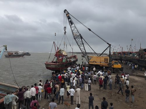 People use a crane to pull a fishing boat ashore on the Arabian Sea coast in Veraval. (Ajit Solanki)