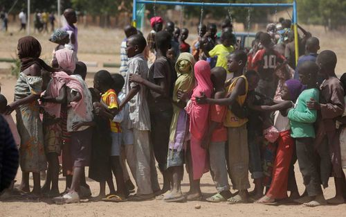 Children displaced after attacks by Boko Haram, line up in the camp of internal displace people, in Yola, Nigeria. (AAP)