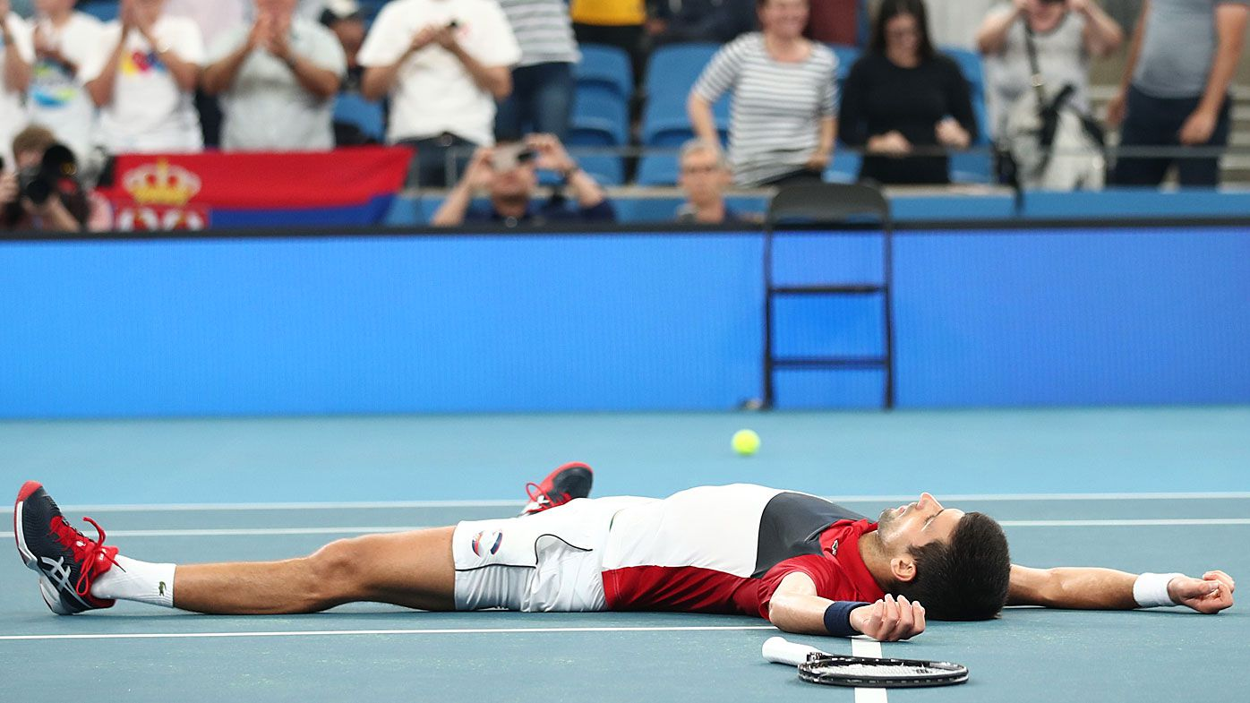Novak Djokovic of Serbia lays on the court celebrating match point during his semi-final singles match against Daniil Medvedev