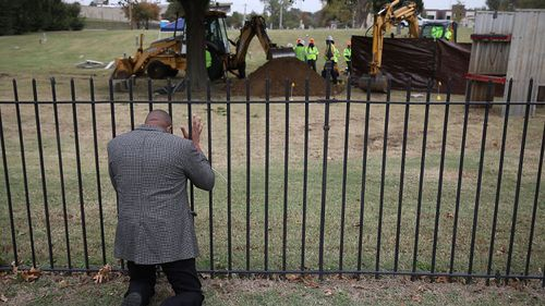 The Rev. Robert Turner prays as crews conduct a test excavation in October, 2020.