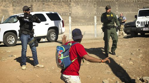 A Central American migrant is stopped by US agents who order him to go back to the Mexican side of the border, after a group of migrants got past Mexican police at the Chaparral crossing in Tijuana, Mexico.