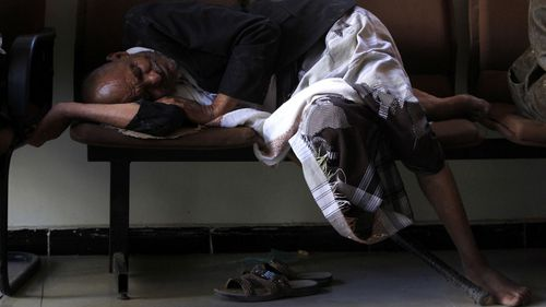 A man sleeps on a seat as he waits for financial assistance from the UN.