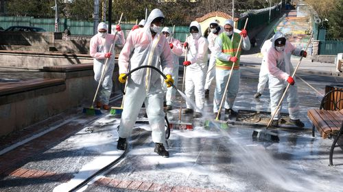 Municipality workers wearing face masks and protective suits disinfect Kugulu public garden amid the coronavirus outbreak, in Ankara, Turkey