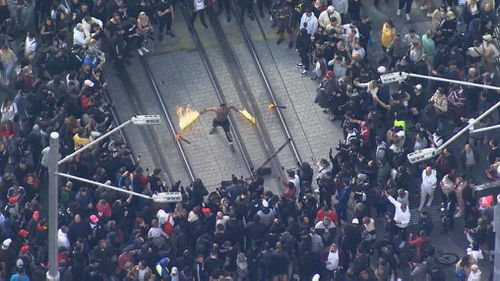 A man with batons lit on fire at the rally in Sydney.