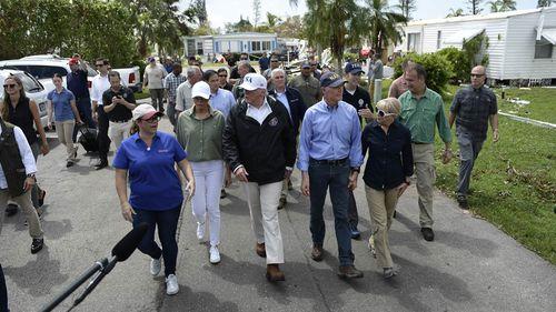 Mr Trump, Melania Trump, Florida Governor Rick Scott and his wife Ann Scott tour a neighbourhood affected by Hurricane Irma, in Naples, Florida. (AFP)