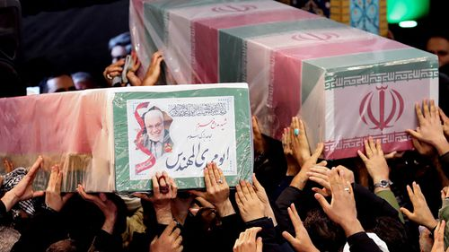 Iranian mourners carrying caskets of slain Iranian military commander Qasem Soleimani (L) and Iraqi paramilitary chief Abu Mahdi al-Muhandis at Tehran University in the Iranian capital