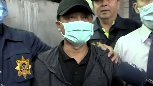 In this image taken from video, Lee Yi-hsiang, the driver of the truck that caused the train accident , offers a public apology as he is led by police in Hualien, Taiwan.