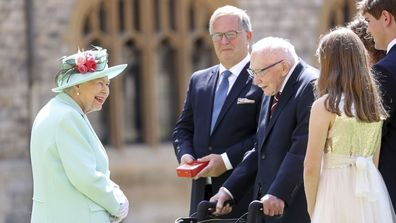 Britain's Queen Elizabeth talks with Captain Sir Thomas Moore and his family after awarding his knighthood during a ceremony at Windsor Castle in Windsor, England, Friday, July 17, 2020