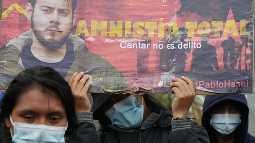 Demonstrators holding a banner supporting rapper Pablo Hasel protest peacefully out side the Spanish consulate in Quito, Ecuador.