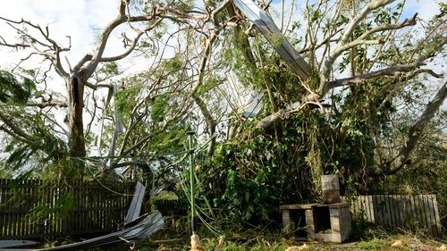 The yard of the holday home is strewn with debris. (AAP)