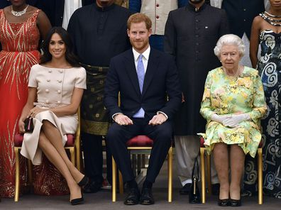 The Queen, Harry and Meghan pose for a group photo at the Queen's Young Leaders Awards Ceremony at Buckingham Palace in London.