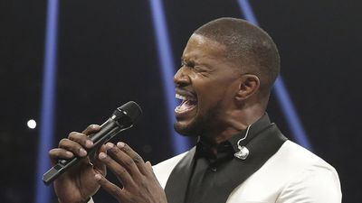 Actor and musician Jamie Foxx sings the national anthem before the start of the fight. (AAP)