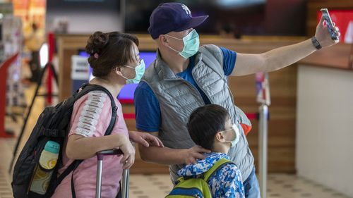 People wearing protective face masks to protect themselves from Coronavirus are seen at Brisbane International Airport in Brisbane, Friday, January 31, 2020
