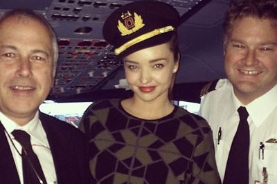 Captain Miranda reporting for duty! The sultry supermodel sidles up to the plane's pilots on her Qantas flight back to Sydney... <br/><br/>Source: Miranda Kerr/Instagram