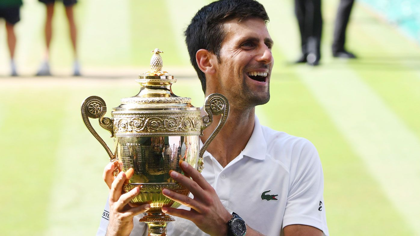 Novak Djokovic celebrates with the Wimbledon trophy.