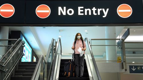 A woman arrives at the domestic terminal at Sydney airport off a Jetstar flight from Melbourne.