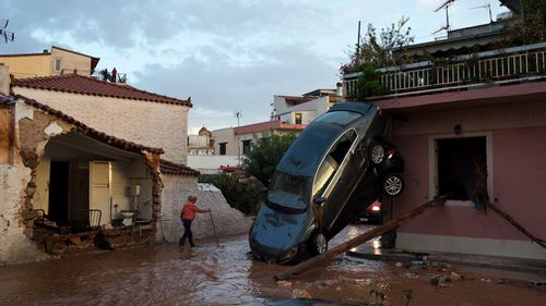 A woman walks on a flooded street next to damaged houses and flipped over cars. (AAP)