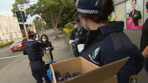 Police in Sydney handing out PPE gear.
