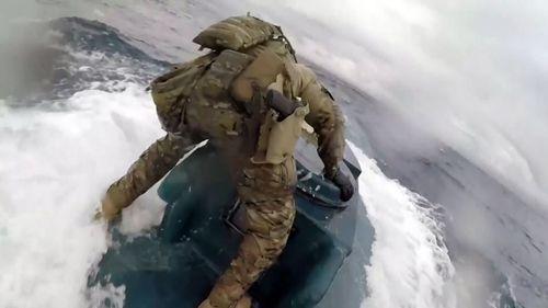 A US Coast Guardsman jumped onto a homemade submarine.