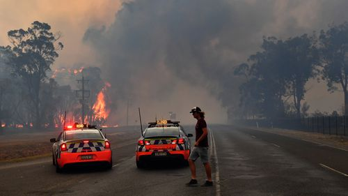Police block the Old Hume Highway as the Green Wattle Fire jumps the road near the town of Tahmoor.