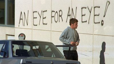 A man parks his car near a message written on the wall of the Royal Albert Hospital in Hobart, Australia, where 28 year old Martin Bryant is in police custody, April 30, 1996. Bryant was charged with murder at a bedside court in the hospital, Tuesday, April 30, 1996.